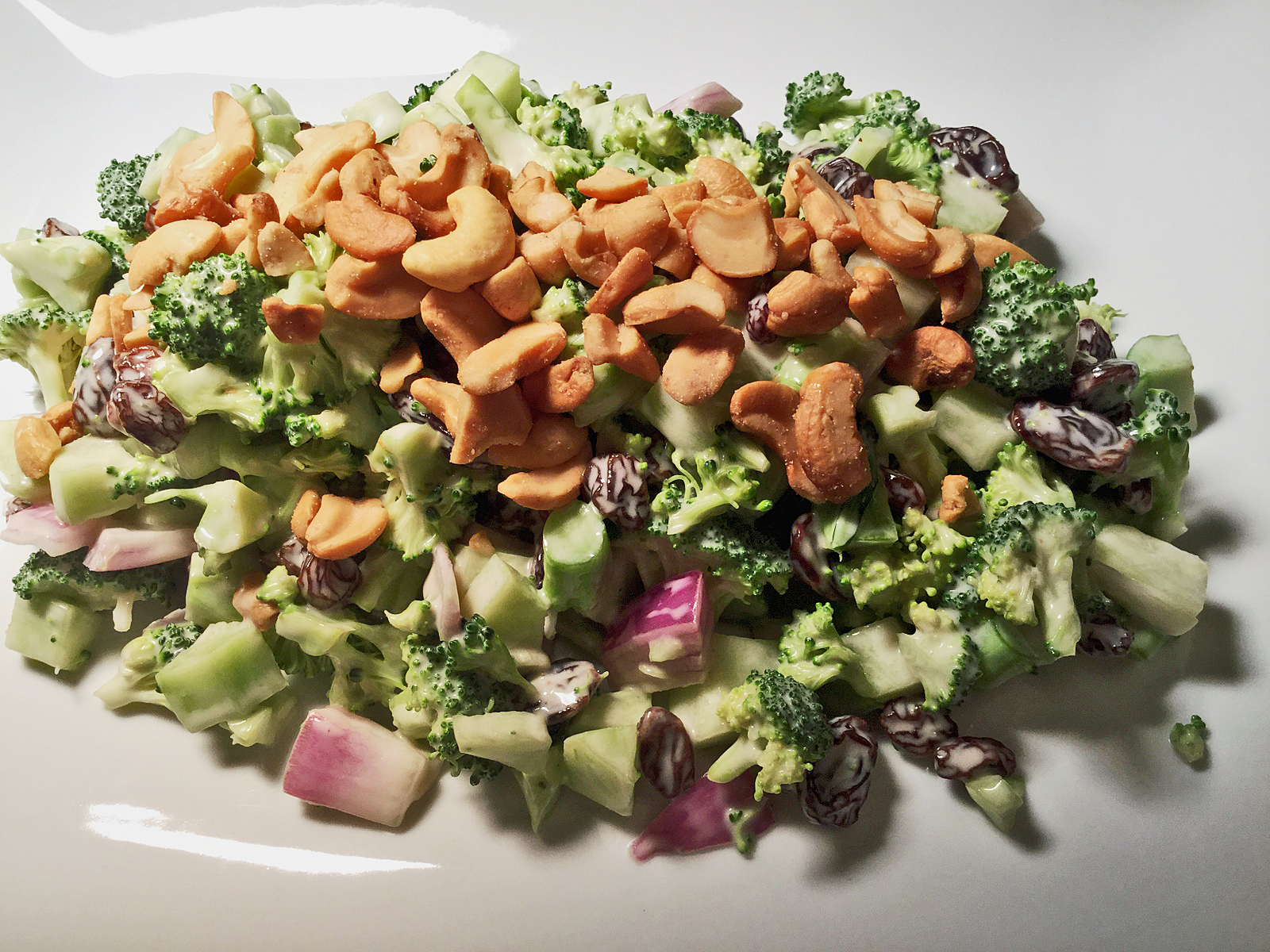 This raw broccoli salad recipe is made with raisins and topped with cashews!